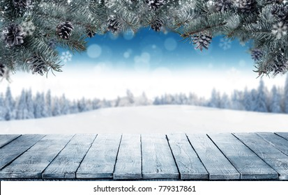 Winter background with empty wooden planks and fir branches. Free space for product placement. Snowy landscape on background