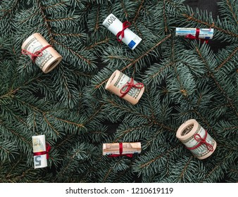 Winter background of fir branches. Money in the form of toys. Christmas card. Top view. Xmas congratulations.