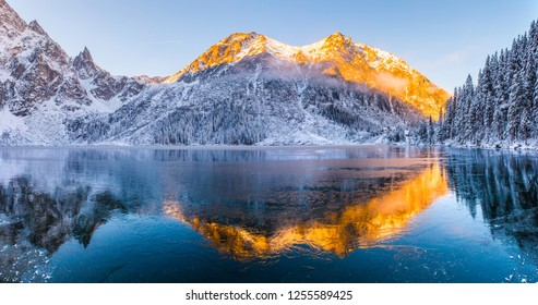 Winter background. Winter landscape with mountains reflected in clear frozen lake. Sunny frosty morning in mountains. Panorama of Tatra mountains at dawn. Morskie oko lake.