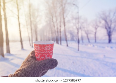 Winter background, red paper disposable cup in hand in a mitten against the background of the winter park
