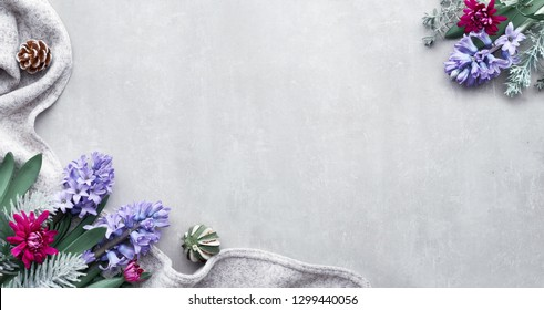 Winter background with seasonal flowers - blue hyacinth and burgundy chrysanthemum on a wool scarf, top view with copy-space, flat lay on stone background