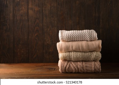 Winter background - Stack of cozy knitted sweaters on old rustic wooden board. Christmas holidays time concept, Selective focus.