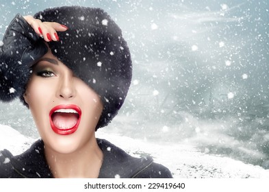 Winter beauty fashion. Beautiful face girl with trendy fur hat gesturing. Emotions. Professional makeup and manicure. High fashion portrait on winter scenery. Snowy day