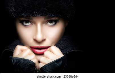 Winter Beauty Fashion. Closeup of gorgeous young woman wearing trendy fur hat and mittens with hands on chin while looking at camera sensually. High fashion portrait isolated on black with copy space.