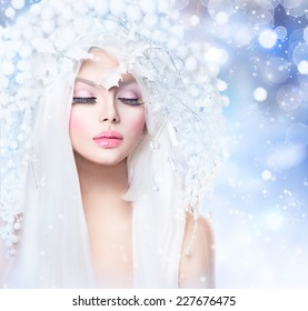 Winter Beauty Woman. Beautiful Fashion Model Girl with Snow Hair style and Make up. Holiday Makeup. Winter Queen with Snow and Ice Hairstyle