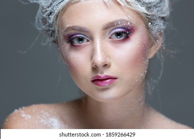 Winter Beauty Woman in clothes made of frozen flowers covered with frost, with snow on her face and shoulders. Christmas Girl Makeup. Make-up the snow Queen. Isolated on a gray background. Close-up.
