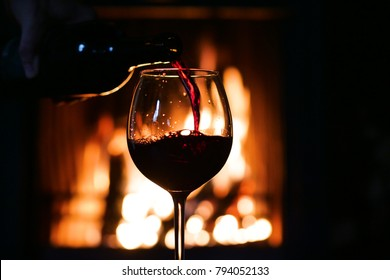 In winter, before the fireplace, is poured, tasted red wine in a glass. Concept of: relax, restaurant, wine, sommelier.
