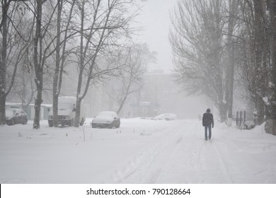 Winter blizzard in the street and the silhouette of a man walking down the street.
