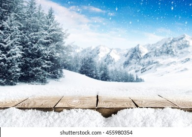 winter blue landscape of alps and brown old table of wood and snow place