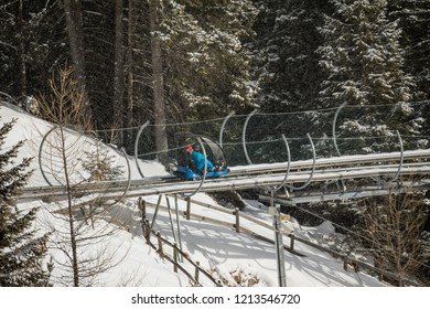 Winter bobsled track in the forest in Dolomites. Boy riding a bobsleigh sitting on a blue truck. Italy