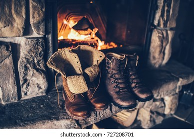 Winter boots in front of a fireplace. Family vintage folk boots drying near the fireside. Warm cozy fireplace in the authentic chalet. Hipster shoes getting warm near the burning fire in a cabin.