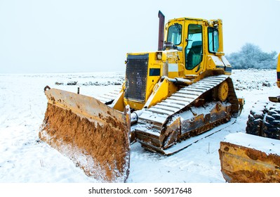 winter break in construction industry- power shovel and bulldozer in snow