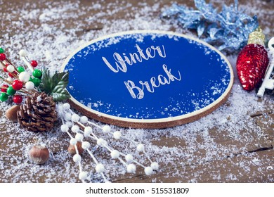 Winter Break Written In Chalk On Blue Chalkboard Holiday Sign Background With Snow And Decorations.