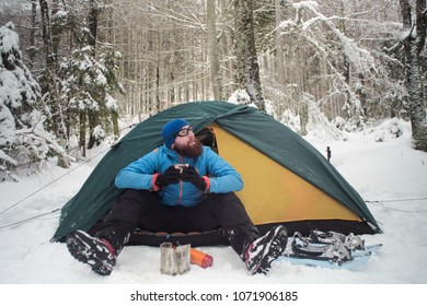 winter camping on snow, hiker sitting in a tent having a cup of hot beverage