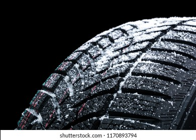 Winter car tires with snow wheel profile structure on black background - Close up.