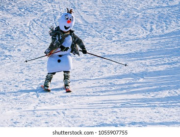 Winter carnival skier rides down the hill in a snowman costume.