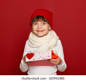 winter, child,  valentine love concept - happy girl in hat with box gift show heart toy symbol on red background