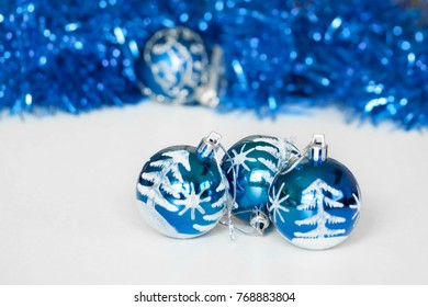 Winter Christmas decoration. Shining blue and white balls on blurred background of sparkling blue garlands.