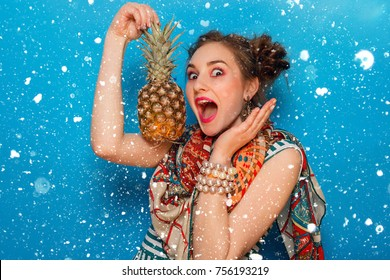 winter, christmas, emotions, people, beauty, fashion and lifestyle concept - The young woman's portrait with happy emotions, Holds pineapple in hands. over snow background