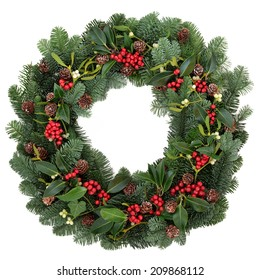 Winter and christmas floral wreath with holly, ivy, mistletoe and spruce fir over white background.