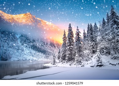 Winter Christmas holiday background. Snowy winter nature landscape in snowfall. Mountains and fir trees in morning sunlight. Xmas time.