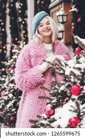 Winter, Christmas holidays concept: outdoor portrait of young beautiful happy smiling woman holding candy cane, wearing light blue beret, pink faux fur coat, posing near decorated new year trees.