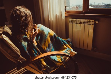 Winter and Christmas holidays concept. Young woman sitting in comfortable modern chair near radiator with mug of tea wrapped in warm plaid blanket. Natural light. Warm atmosphere. Cozy home