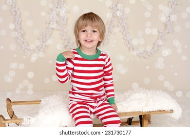 Winter or Christmas Holidays: laughing, smiling, happy child, kid in red and green striped pj pajamas on wood sled in fake snow, snowflakes