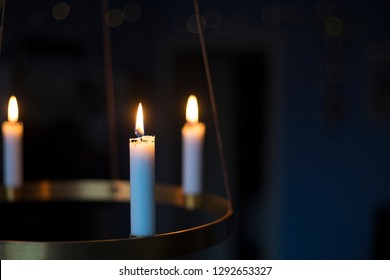Winter, christmas or hygge background with candles glowing on a golden advent chandelier.