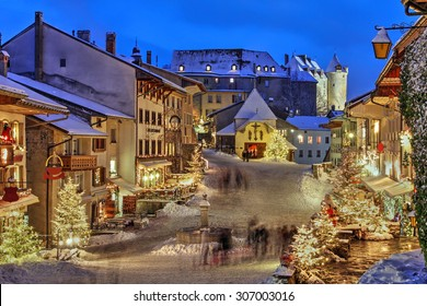 Winter (Christmas) in the medieval town of Gruyeres, Fribourg canton, Switzerland. In the background looming over is the Chateau de Gruyere.