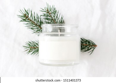 Winter, Christmas mockup-scene. Closeup of candle in glass jar with blank label. Blurred green fir tree branch, white linen tablecloth backgound. Front view.