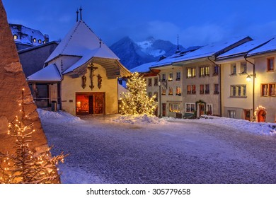 Winter (Christmas) night scene in the medieval town of Gruyeres, district of Gruyere, Fribourg canton, Switzerland, where the famous cheese bearing the name is made.