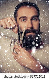 winter, christmas, people concept- Man Cutting Beard against a over snow background portrait