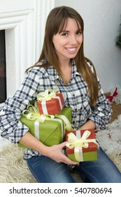 winter, christmas, people concept- Young attractive woman in casual shirt sitting on floor with near christmas tree and fireplace.