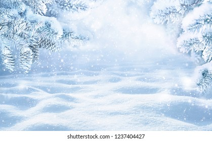 Winter Christmas scenic background with copy space. Snow landscape with spruce branches with cones covered snow close-up, snowdrifts and falling snow on nature outdoors, toned blue.