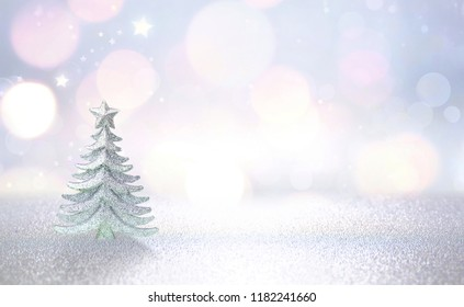 Winter christmas scenic background. Silvery small Christmas tree on a blurred snowy defocused background in blue and pink tones with copy space.