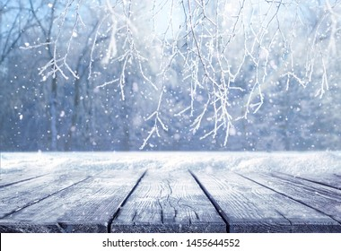 Winter christmas scenic landscape with copy space. Empty wooden flooring, stage platform, white birch branches covered with snow in forest on nature, soft focus, defocused background.