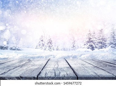 Winter christmas scenic landscape with copy space. Wooden flooring strewn with snow in forest  with fir-trees covered with snow on nature.