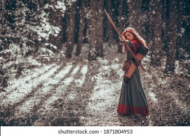 Winter Christmas tales. A beautiful red-haired girl archer of the Middle Ages stands in a winter forest. Fantasy world.