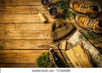 Winter or christmas weekend in country cottage (cabin) concept. Boots, warm hat, hot drinks and firewood. Rustic layout, from above (flat lay). Vintage wooden background with free text (copy) space.
