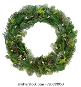 Winter and christmas wreath with mistletoe, cedar, juniper fir, blue spruce and ivy leaves on white background.