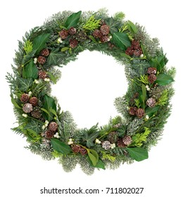Winter and christmas wreath with pine cones, mistletoe, blue spruce, cedar, juniper fir and ivy leaves on white background.