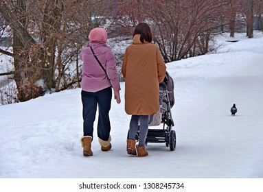 Winter. City. Two girls with a stroller walk along the snowy path, they are accompanied by a dove.