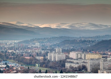 Winter cityscape of Eastern European communist era tower blocks in Miskolc city outskirts with forested hills and sunlit snow-capped Bukk Mountains in North Hungarian Mountain Range, Hungary Europe