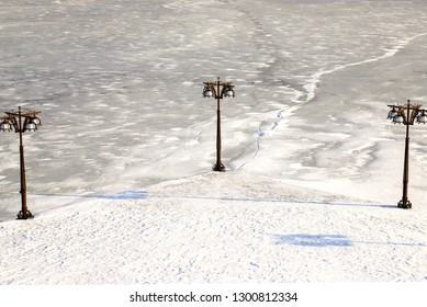 Winter cityscape of a river covered with ice, snow. and embankment with vintage metal lantern, Dnepropetrovsk, Dnipro city , Ukraine,