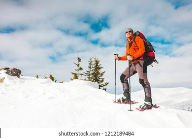 Winter climbing the mountain. A man in snowshoes is climbing to the top. Winter ascent. A mountaineer with a backpack and trekking sticks. Equipment for winter hiking.