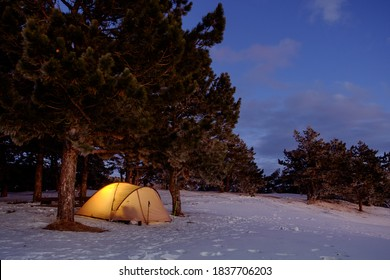 Winter climbing in the mountains. Tourist tent at the top