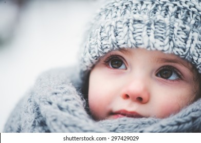 winter close up outdoor portrait of adorable dreamy baby girl in grey knitted hat and scarf