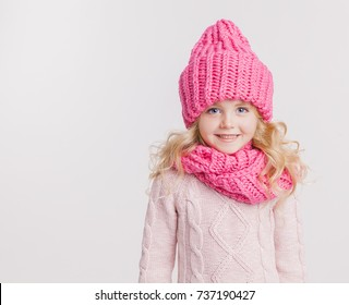Winter clothes. Portrait of little curly girl in knitted pink winter hat and scarf