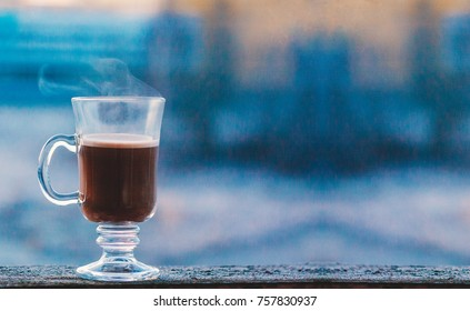 Winter coffee in a transparent cup. Winter cacao. Hot drink outside. Winter season.